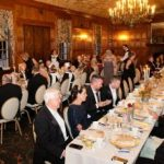 Elegantly dressed guests seated at parallel dining tables in a wood-paneled dining room at KET's Fabby Abbey Ball 2019