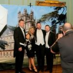 Guests and photographer in front of a Downton Abbey backdrop at KET's Fabby Abbey Ball 2019