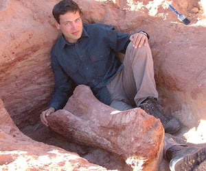 A man sits next to a relic unearthed at an archeological dig
