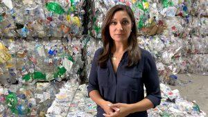 PBS Newshour correspondent Amna Nawaz stands among bundles of used plastic bottles