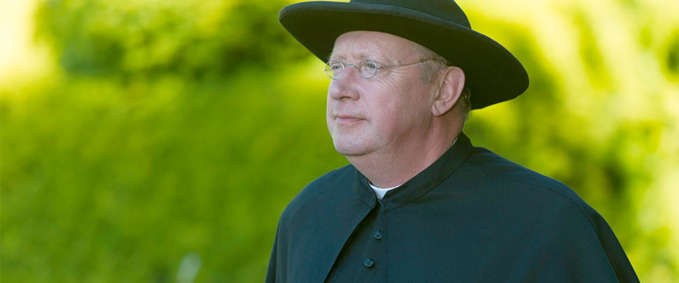 Father Brown in front of a green background