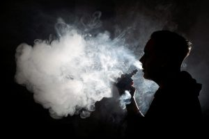 A person uses a vaping device in silhouette.