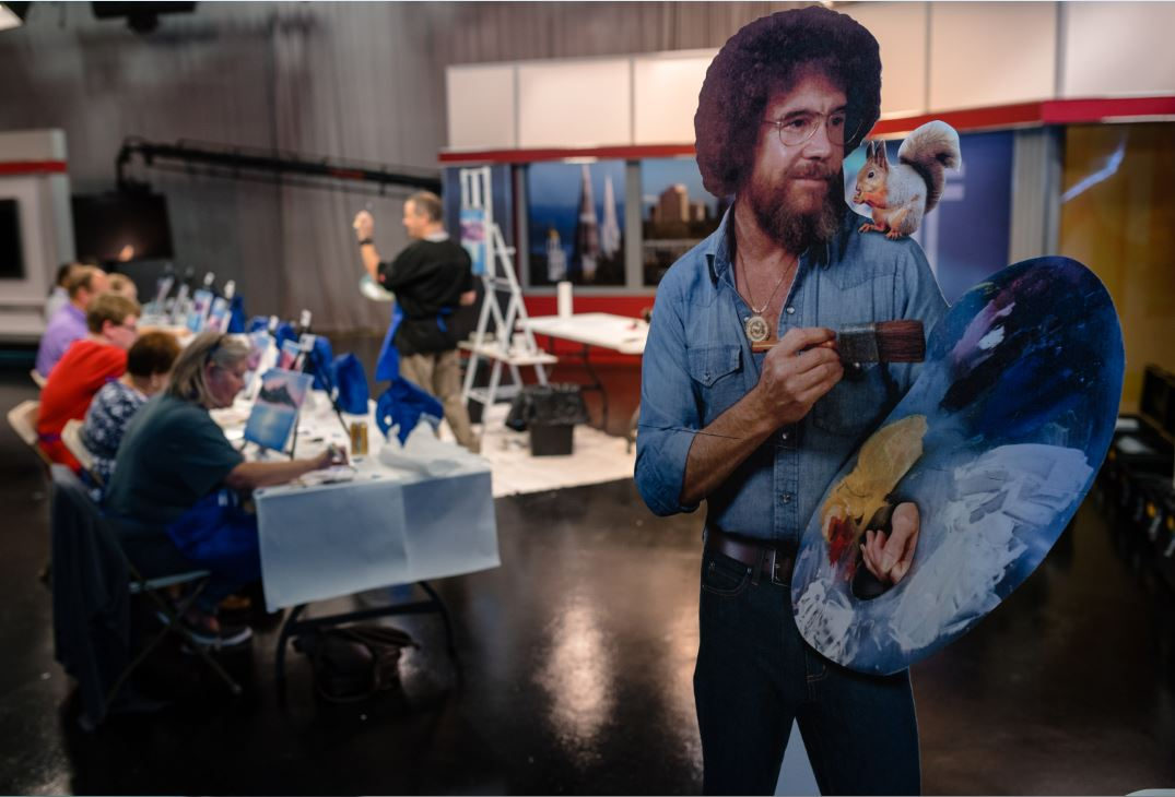 People attending a Bob Ross painting party