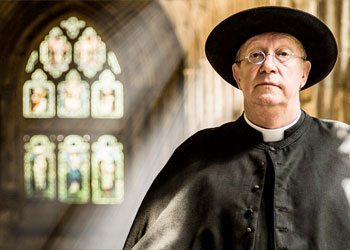 Father Brown standing in a church