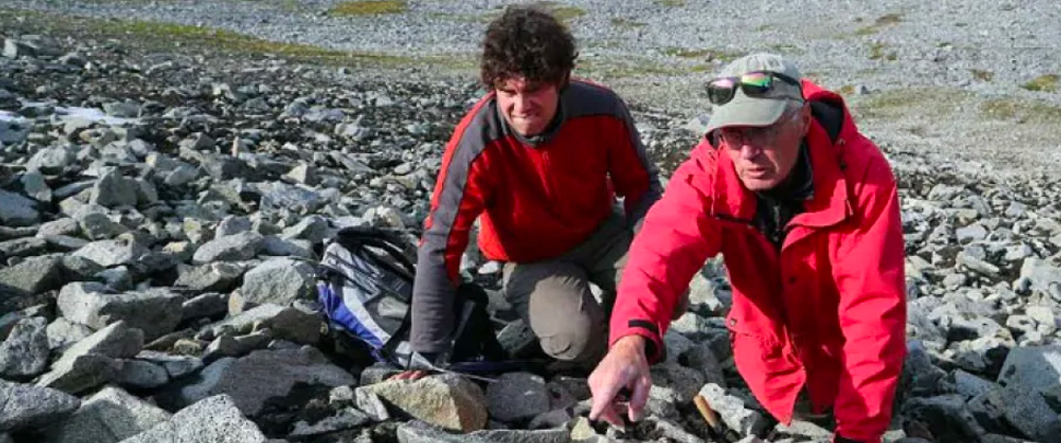 Scientists exploring rocky terrain uncovered by melting ice in the Yukon