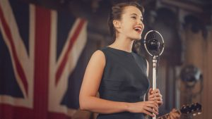 Julia Brown (as Lois Bennett) singing on stage with the flag of Great Britain in the background