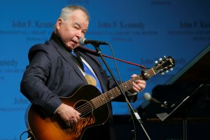 John Prine singing and playing acoustic guitar during a ceremony at the John F. Kennedy Library in Boston
