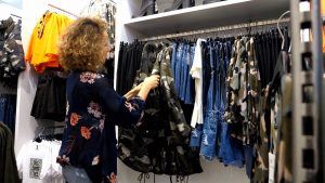 Shop owner organizing clothing on a store rack