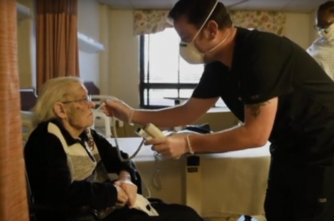 A resident in a nursing home gets her temperature taken.