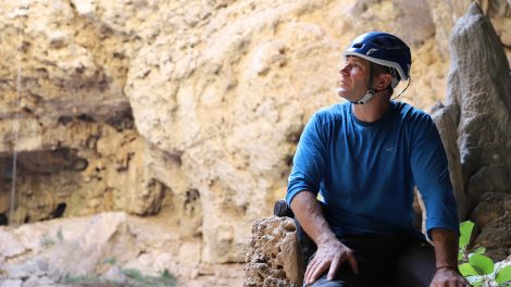 Steve Backshall looking up the rock face in Oman.