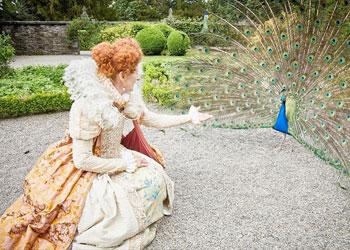 Queen Elizabeth reaching toward a peacock