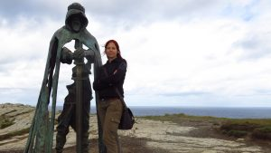 A woman posing with the abstract bronze sculpture, Gallos, inspired by King Arthur