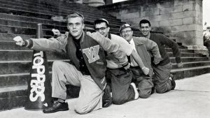 Four members of The Hilltoppers posing together at the bottom of a stairway outside a campus building