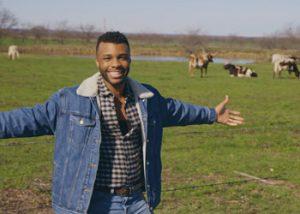 Prideland host Dyllón Burnside posing in front of a field of longhorn cattle in Texas