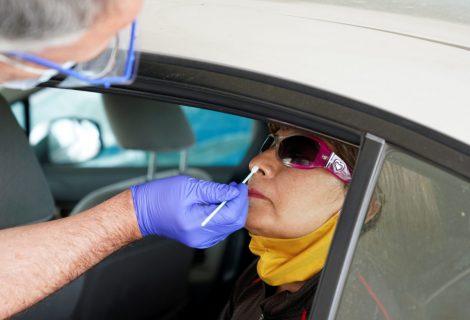 A woman receives a nasal swab COVID-19 test.