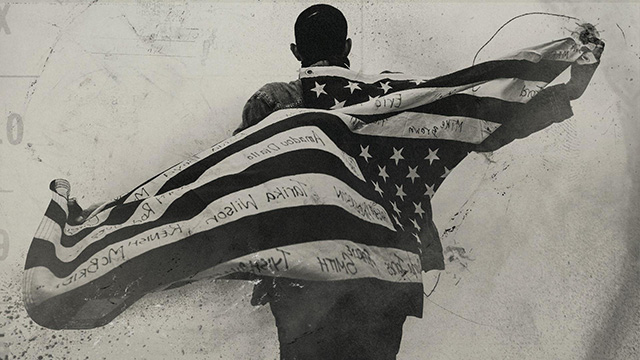 African American man with american flag behind his back