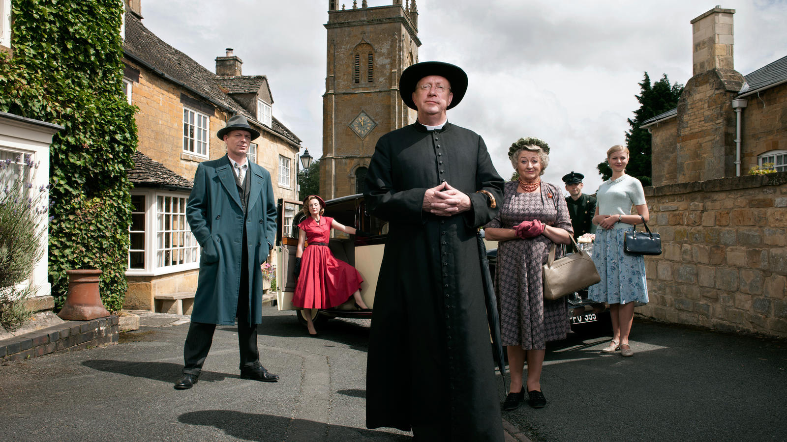 The cast of Father Brown standing together in the town center