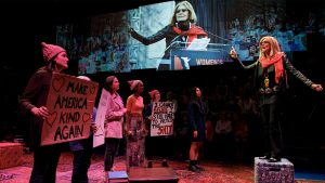 Christine Lahti and company on stage in a scene depicting the 2017 Women's March.