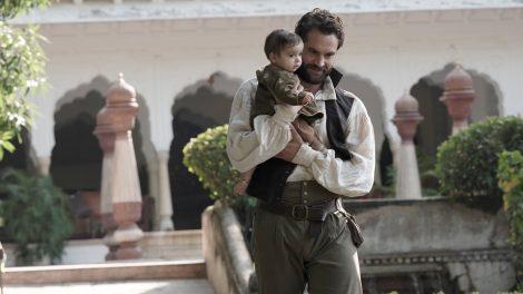 Tom Bateman as John Beecham, holding a baby