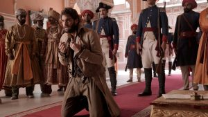 Tom Bateman as John Beecham with chains around his wrists, kneeling in front of a group of soldiers and other men