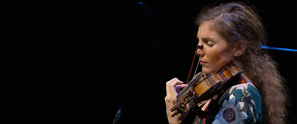 A woman playing a violin on stage
