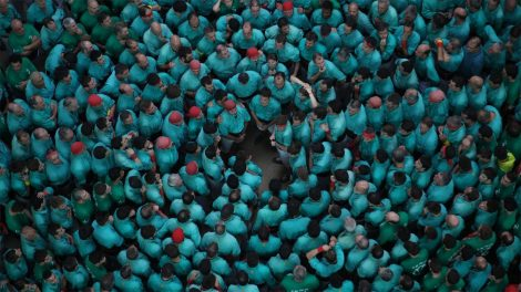 A large group of men in light blue shirts standing in concentric circles to form the base in a human tower building contest