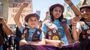 Three young girls, members of The Radical Monarchs, marching at a rally