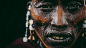 Close up of an African man with lines of orange color painted over his cheeks and nose