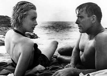 Deborah Kerr as Karen Holmes and Burt Lancaster as Sgt. Milton Warden lying next to each other on the beach in a black-and-white still from From Here to Eternity
