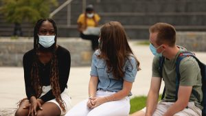 College students meet outdoors while wearing masks.