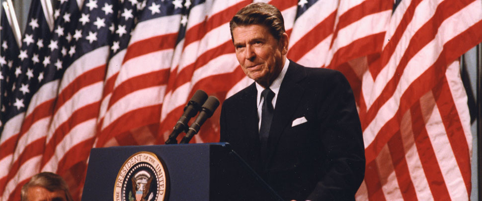 President Ronald Reagan in front of a row of American flags