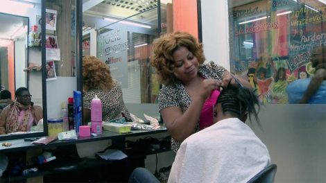 Beautician braiding a client's hair in a small beauty shop