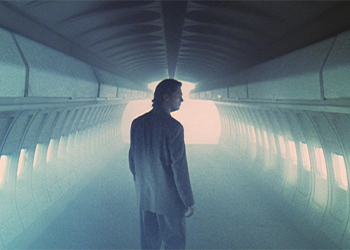 A man standing in an empty, fog-filled airplane cabin