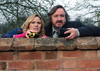 Lu Shakespeare and Frank Hathaway looking over a stone wall