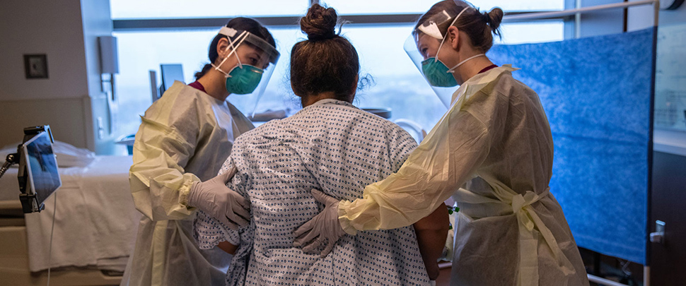 Hospital workers help COVID-19 patient and mother Zully to take her first steps after being removed from a ventilator at a Stamford Hospital ICU on April 24, 2020 in Stamford, Connecticut.