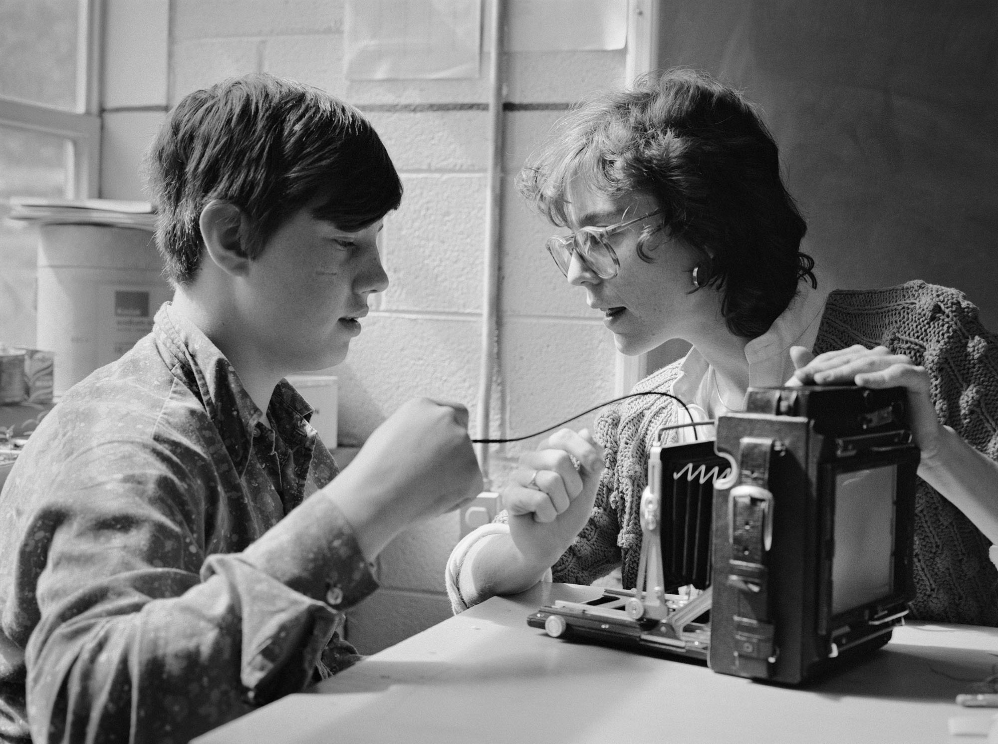 A black-and-white photograph of a boy holding a wire attached to an old camera while seated at a table next to his teacher, Wendy Ewald, who has her hand on the top of the camera.