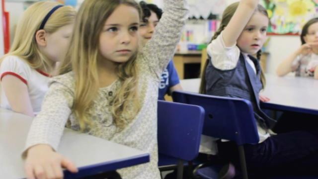 Children in school wth one raising her hand