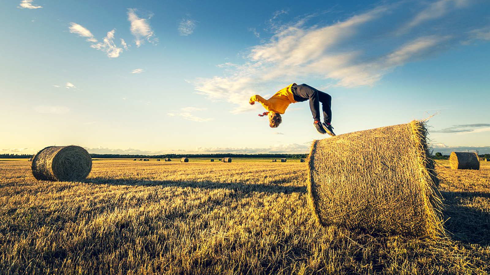 A young man in a yellow shirt does a back flip off a hay bale in a field with other hale bales and a blue sky dotted with clouds in the background.