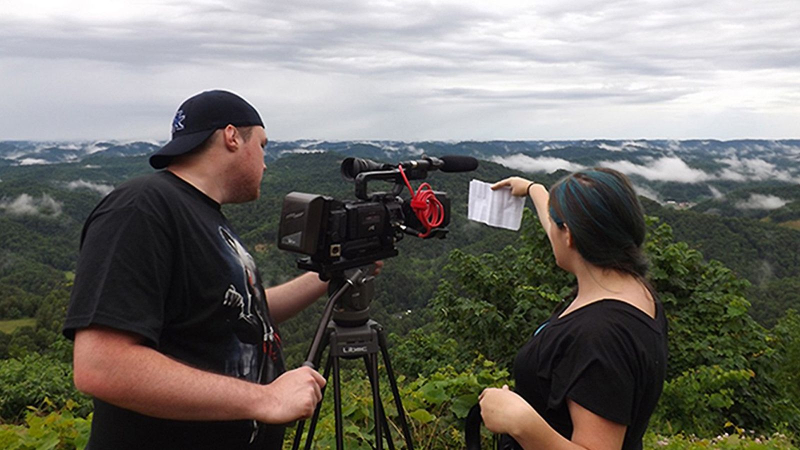 On the left, a man dressed in a backward black baseball cap and t-shirt on the left uses a video camera on a tripod and a woman on the right with blue-streaked dark hair and in a black t-shirt holds a piece of paper in front of the videocamera lens. In the background are green trees and darker green hills with clouds nestled among them.