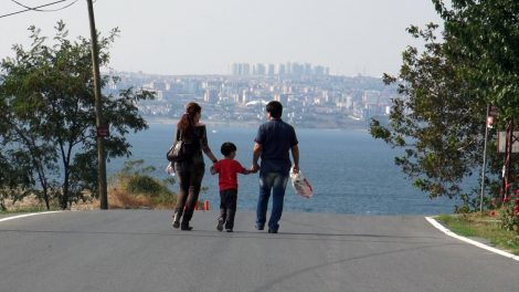 A couple with their young child holding hands and walking down the middle of an empty street toward the waterfront with a city skyline in the background