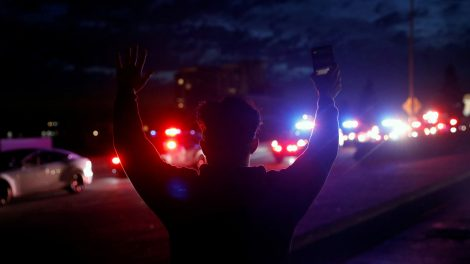 A demonstrator raises his arms towards a convoy of police vehicles during a protest in Oakland, California in May 2020 after the death of George Floyd.