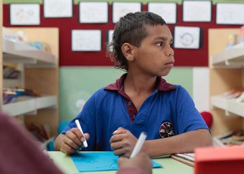 Dujuan, a 10-year-old boy, sitting at a table in a classroom