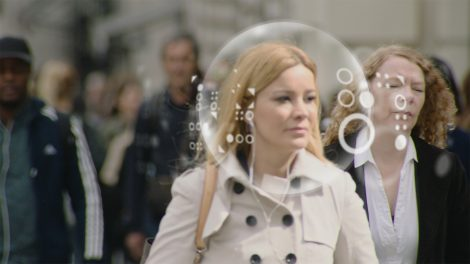 A woman walking in a crowded street with a bubble around her head