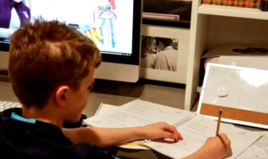A young student does a class assignment from home.