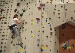 A climber navigating an indoor climbing wall at Vertical eXcape in Bowling Green