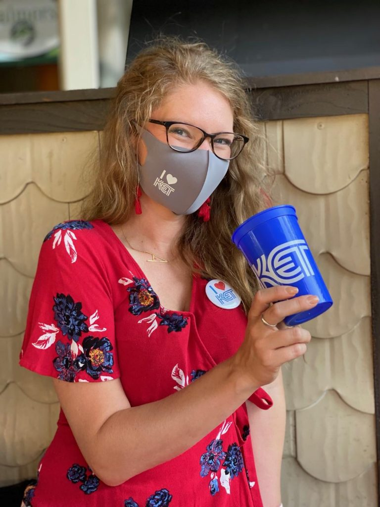 Junior League of Lexington volunteer with a KET face mask, button, and cup