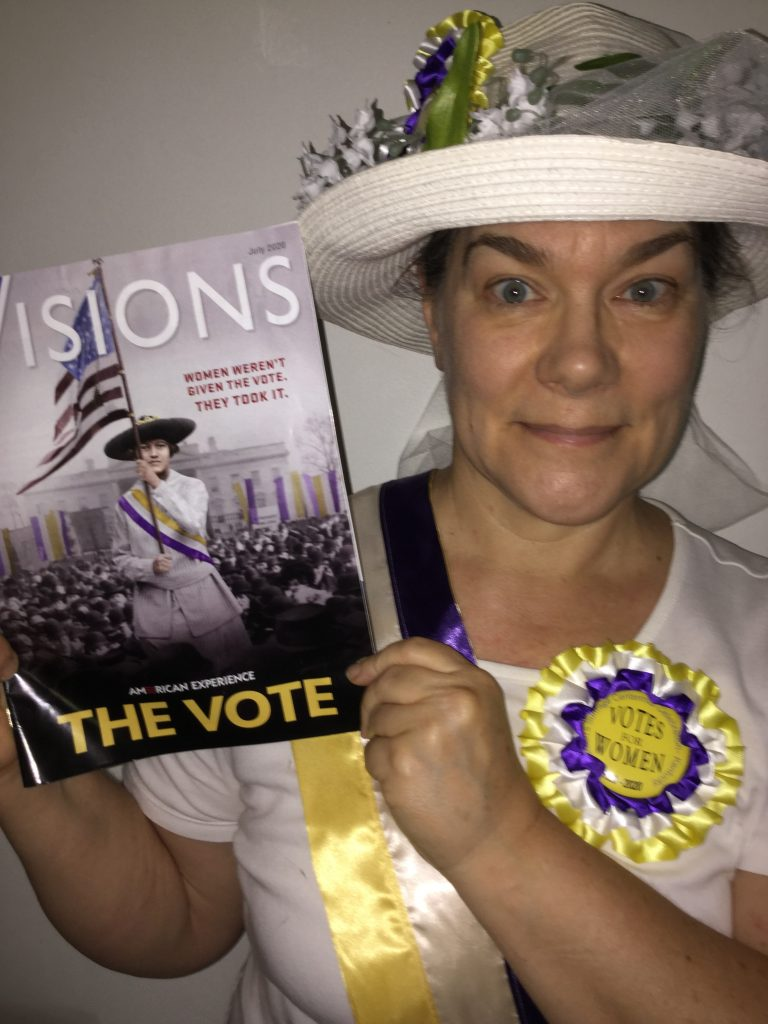 Woman in suffragette costume holding the July issue of KET Visions with suffragette photo on the cover promoting American Experience: The Vote