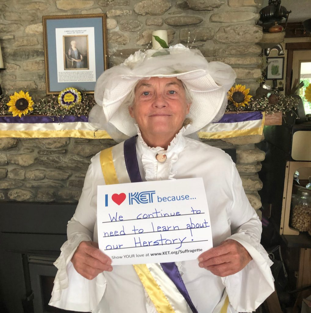 """Woman in suffragette costume holding sign that says """"I heart KET because we continue to need to learn about our Herstory!"""""""