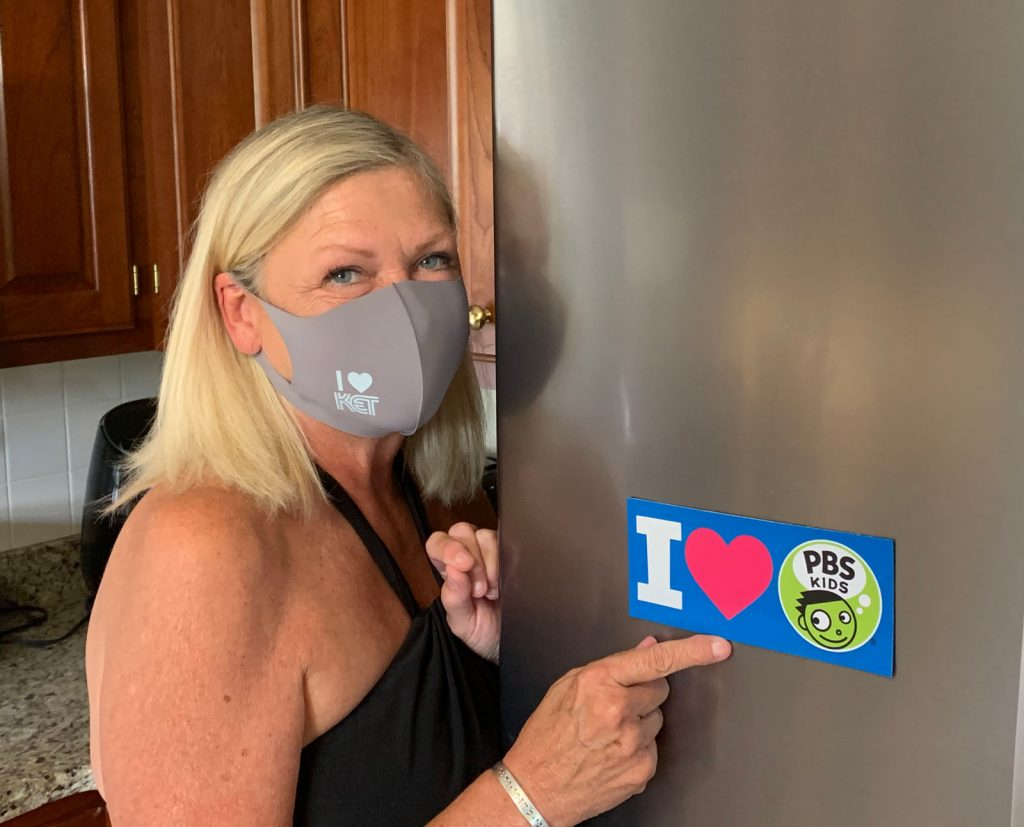 Woman wearing a KET facemask and pointing to an I heart PBS Kids sticker on a refrigerator door.