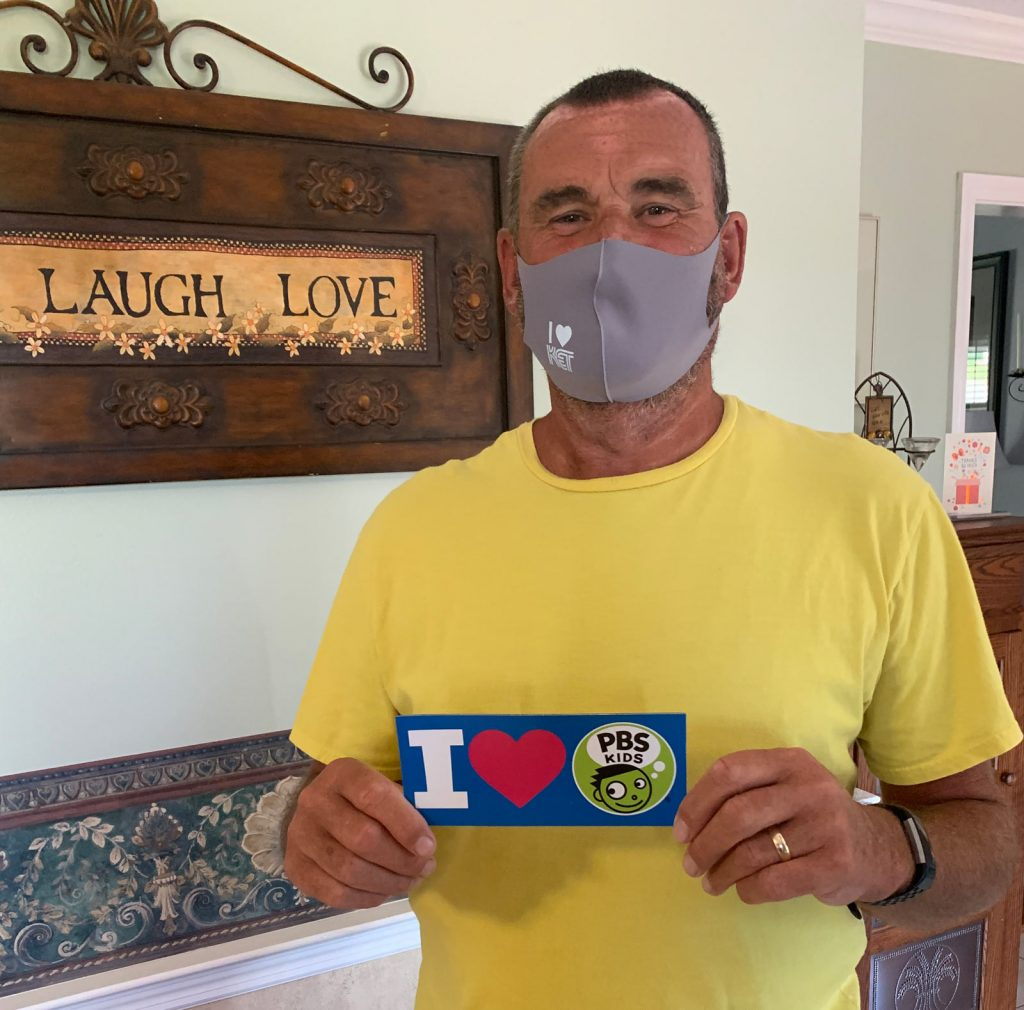 """Man with a KET facemask and an """"I heart PBS Kids"""" sticker"""